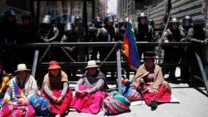 Apoiadoras do ex-presidente Evo Morales em frente a um bloqueio policial em La Paz