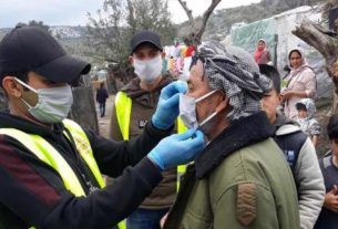 Voluntários da ONG Team Humanity distribuem máscaras no superlotado campo de refugiados de Moria