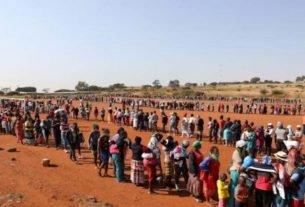 Pessoas fazem fila para receber alimentos em Laudium, nos subúrbios de Petrória, na África do Sul, em meio à pandemia do novo coronavírus
