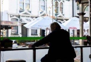 Homem aguarda pedido em café da Nova Zelândia após restrições domésticas serem suspensas