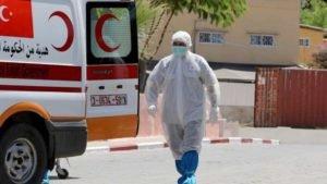 Agente de saúde palestino caminha em direção a ambulância após morte de idoso por covid-19 em Gaza