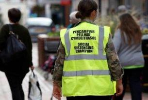 Funcionária de conselho com colete de segurança em Wrexham, no Reino Unido