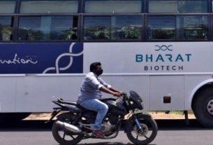 Homem passa de moto por ônibus da empresa indiana Bharat Biotch em frente a sede da companhia em Hyderabad, na Índia